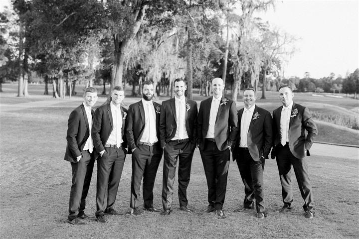 Groom and groomsmen standing on golf course